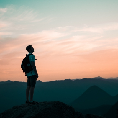man standing on mountain wearing backpack looking up to pink sky