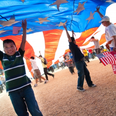 brown kid holding up large american flag