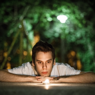 young man with head on folded hands gazing at candle