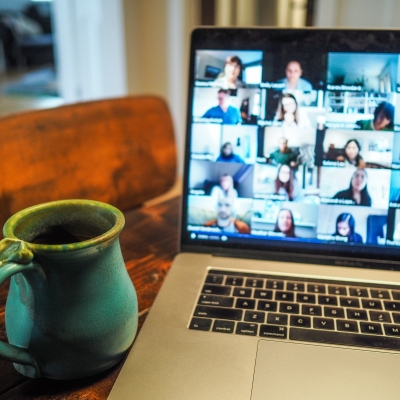 a laptop with a zoom screen full of people is set on a table with a mug next to it