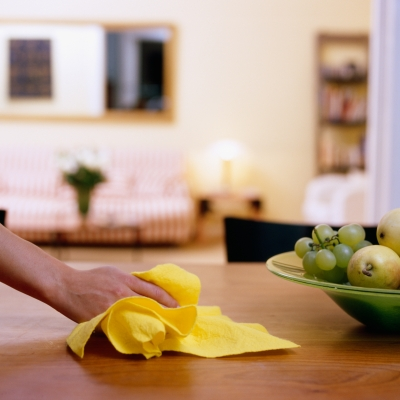 hand holding yellow rag cleaning wooden table with bowl of apples