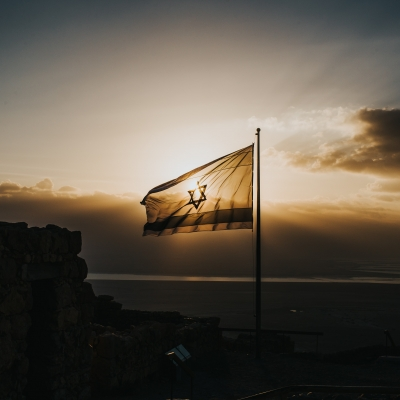 israeli flag with sunlight from a sunset streaming through with gray clouds around