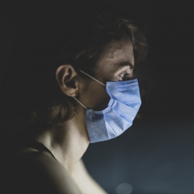The profile of a person in a purple surgical mask is pictured from the shoulders up. The background is dark.