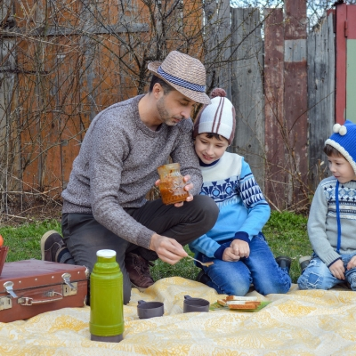dad and two sons having a picnic with apples bread and jam