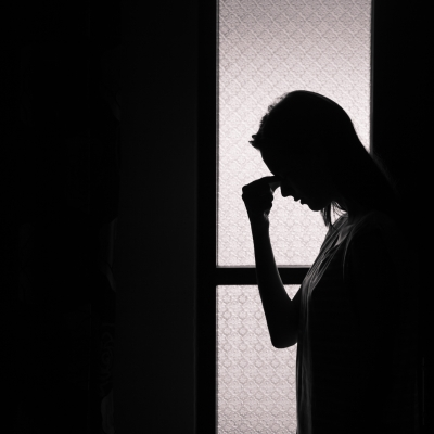 sillouette of person with head bowed in grief