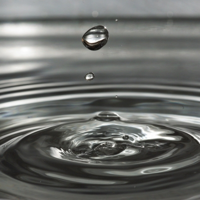 black and white photo of drop of water falling onto water surface and rippling