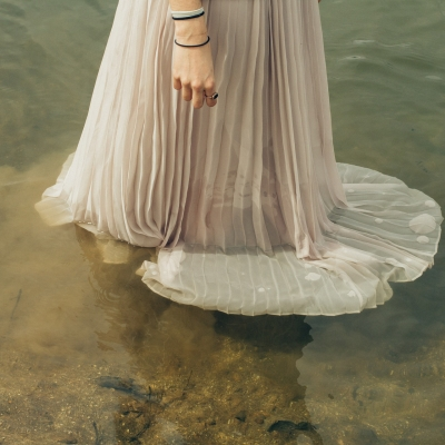 a person standing in a pool of water wearing a beige, flowing skirt. The skirt is partly submerged in the water and is translucent. The person has two black hair ties on their wrist and a ring on their pointer finger.