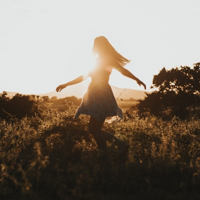 woman dancing in field with sunlight behind her