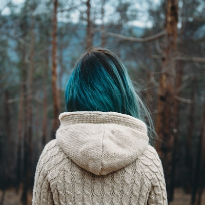 person with blue hair shown from behind facing forest of bare trees