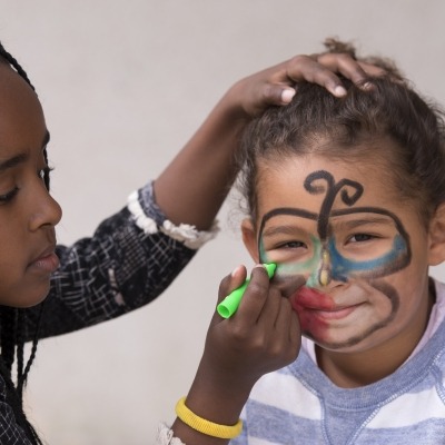black girl drawing mask on younger child's face