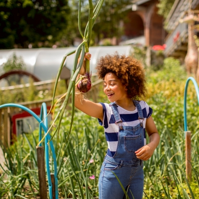 black girl holding vegetable in a garden and smiling