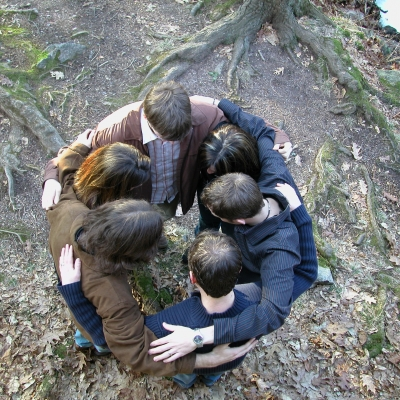 group of people hugging outside in a circle