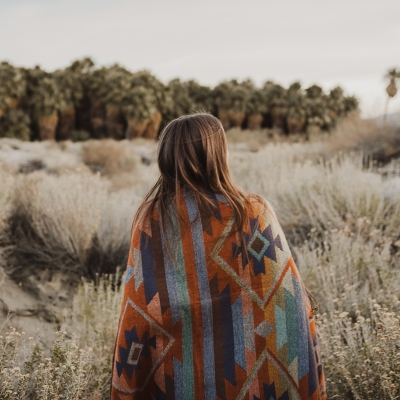 woman wearing patterned cape walking in wilderness
