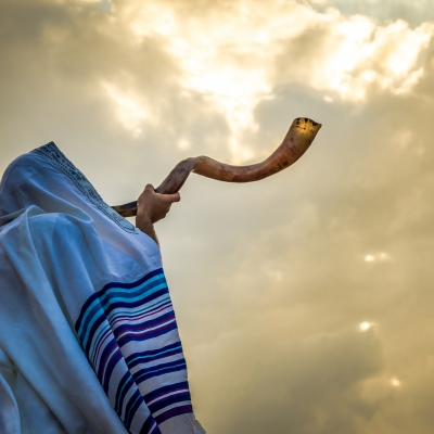 man covered in tallit blowing large spiraling shofar facing a sunlit cloudy sky