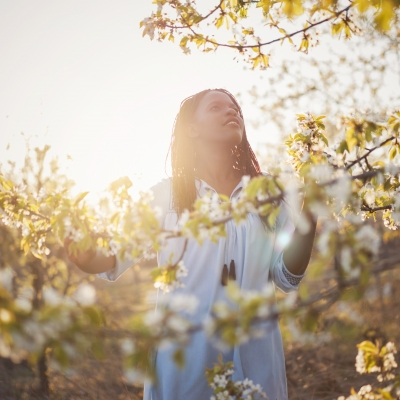 black woman standing by flowering tree looking into sunlit sky contemplatively