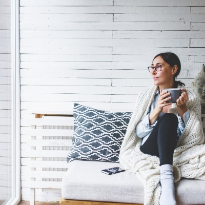 woman wearing glasses holding mug sitting on sofa in enclosed porch looking outside