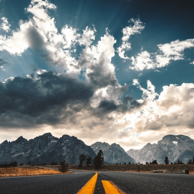 road leading to mountains with with clouds in the sky