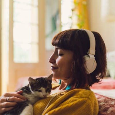 woman with eyes closed, wearing headphones, holding kitten