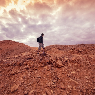 young person with backpack hiking through rocky desert with bright clouds above