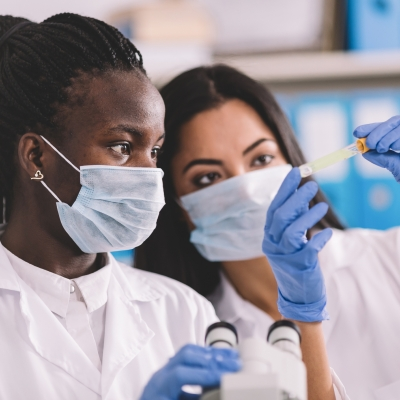 Two people wearing white lab coats, masks, and blue gloves are looking at a vile of liquid. One is a black woman with her long dark braids pulled into a ponytail. The other is a tan woman with straight dark hair.