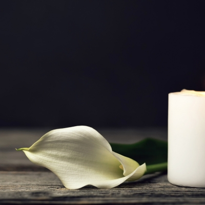 a single white candle sits off to the right, with a small flame. next to it in the center of the photo is a cut, white calla lily resting on the surface