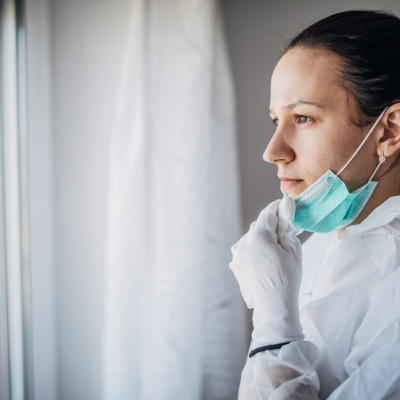 we see the profile of a person with dark brown hair pulled back in a pony tail. They have fair skin and are wearing a medical gown and gloves. They are pulling the mask down off of their face over their chin and looking off to the left out of a window.