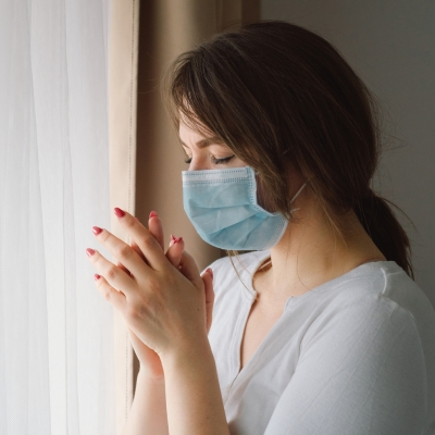 light-skinned woman with brown hair wearing mask and eyes closed holding hands together as if praying next to white curtain indoors