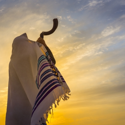 a person blows shofar against a yellow and purple sky wrapped in a tallis
