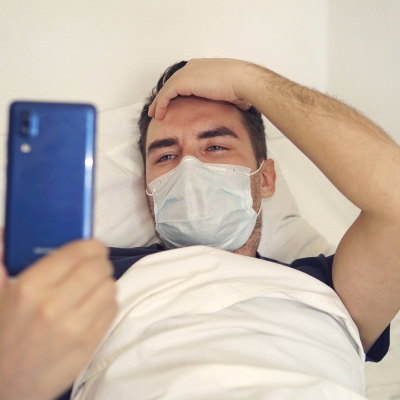 A person lies in bed with a mask over their nose and mouth and their right hand on their forehead. In their left hand they are holding up a blue smartphone facing them.