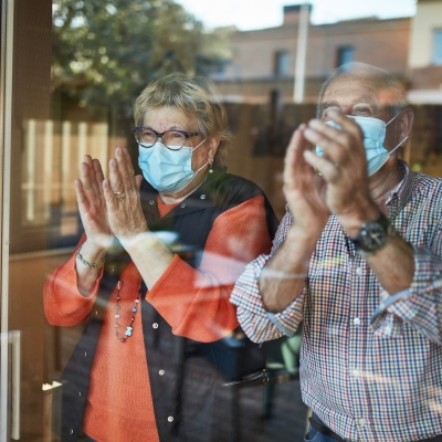 older man and woman wearing masks shown behind the window of their home clapping and smiling