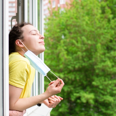 A white brunette leans outside an open window, holding a mask that is hanging off their ear, and taking a deep breath