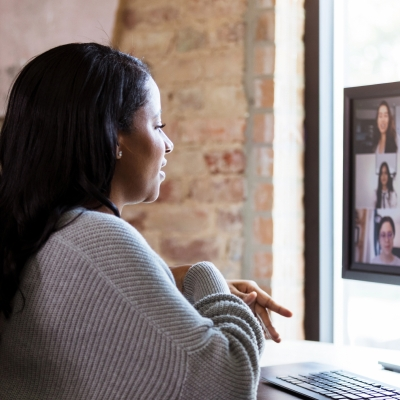 A person with long brown hair and dark skin in a grey sweater sits in front of a computer screen. We can see their profile as they look at the screen which is filled with nine zoom boxes, six of which we can see fully. There are individuals in each of the zoom boxes as if they are in a meeting together.