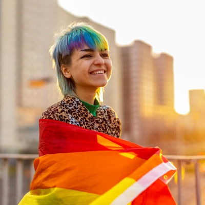 a teen with short, rainbow mullet is wrapped in a rainbow flag and is smiling as the sun sets in the background