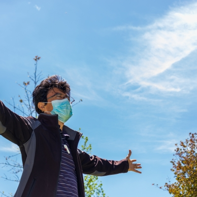 man with brown hair and glasses and mask standing outside with eyes closed and arms open wide to bright blue sky