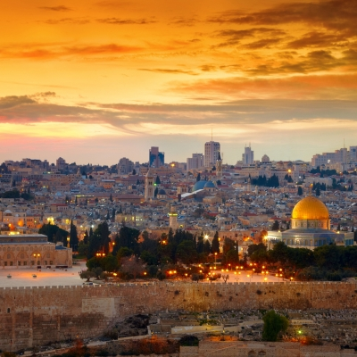 view of jerusalem with orange sunset and dome of the rock golden and lit up