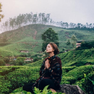woman in forest with eyes closed and hands pressed together in prayer