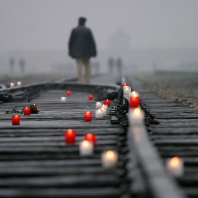 old man in the distance walking on train tracks. in the foreground are white and red lit candles speckling the tracks.