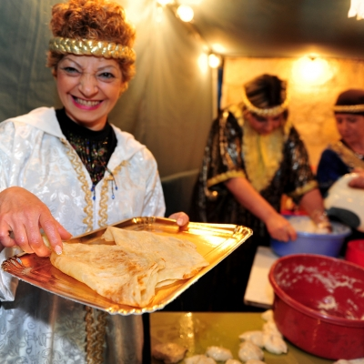 israeli woman holding tray of mufleta with two other women in the background. they are dressed in traditional morrocan garb with gold headpieces and dressy shirts.
