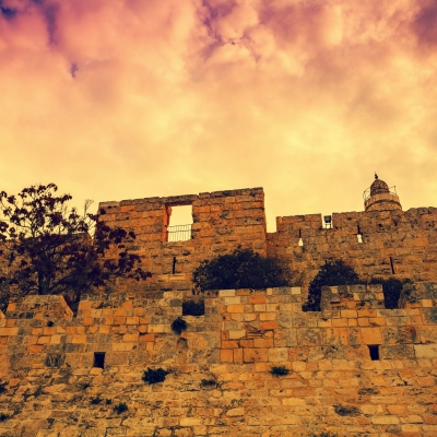 wall in old city of jerusalem under pink cloudy sunset sky