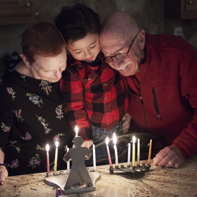 an image of two elderly adults standing on either side of a child. They are standing in front of two hanukkah memorahs and three candles are lit, indicating it is the second night of hanukkah.