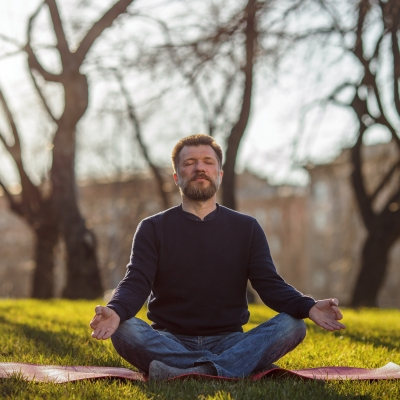 white man with graying beard sitting in a sunny field meditating with eyes closed
