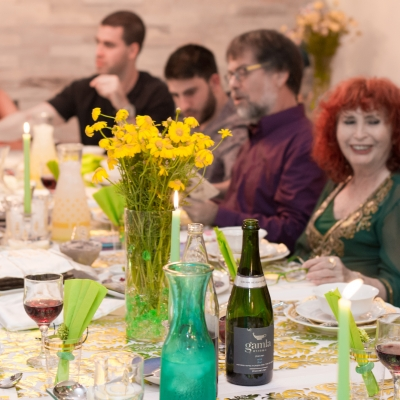 group of people sitting at seder table with yellow flowers in a vase and bottle of wine