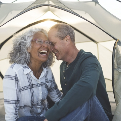 older interracial couple laughing in an outdoor tent