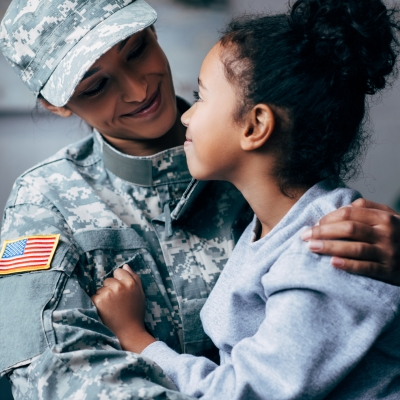 brown-skinned woman in american military uniform holding daughter smiling at each other