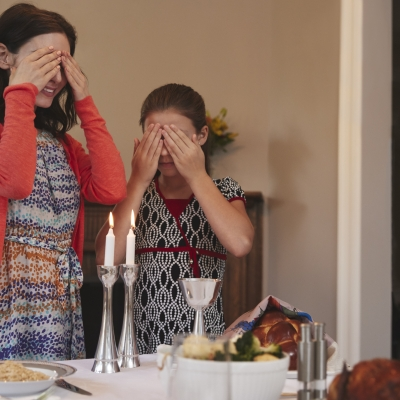 two girls one taller than the other with hands over their eyes blessing shabbat candles, with kiddush cup and challah in view