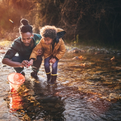 black man and son walking in forest stream