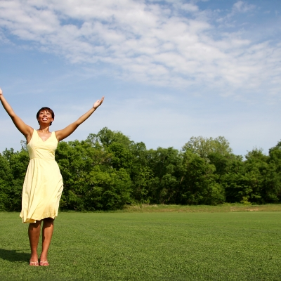 A Black woman wearing a yellow sun dress stands in a green field lined with trees and holds her hands above her head in a V shape