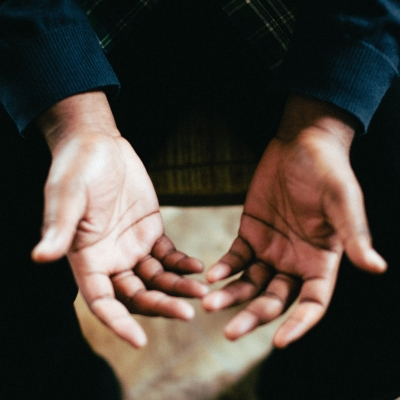 close up of light-skinned person's hands open on lap. person is wearing dark shirt and pants, face not shown.