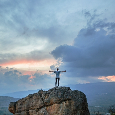 person shown from distance standing on large rock with arms open to sky with large clouds