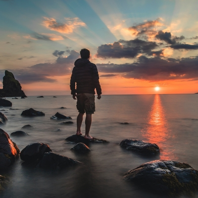 man standing at ocean edge with feet in water and rocks around looking at sunset